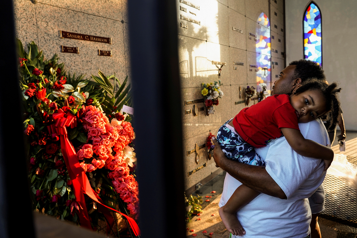A mourner carries a child as he pays his respects at Houston Memorial Gardens cemetery where George Floyd was buried. [Go Nakamura/Reuters]