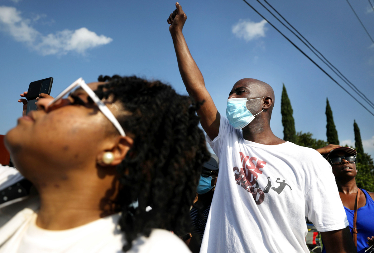 People watch the George Floyd funeral procession enter Houston Memorial Gardens Cemetery. [Mario Tama/Getty Images/AFP]