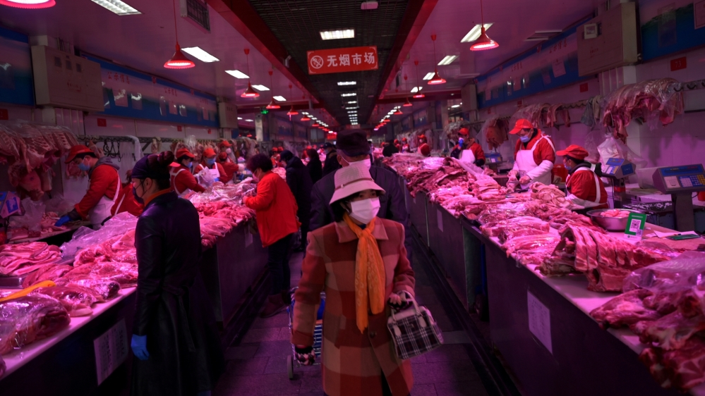 Customers wearing face masks buy pork meat at the Xinfadi wholesale market, as the country is hit by an outbreak of the novel coronavirus disease (COVID-19), in Beijing