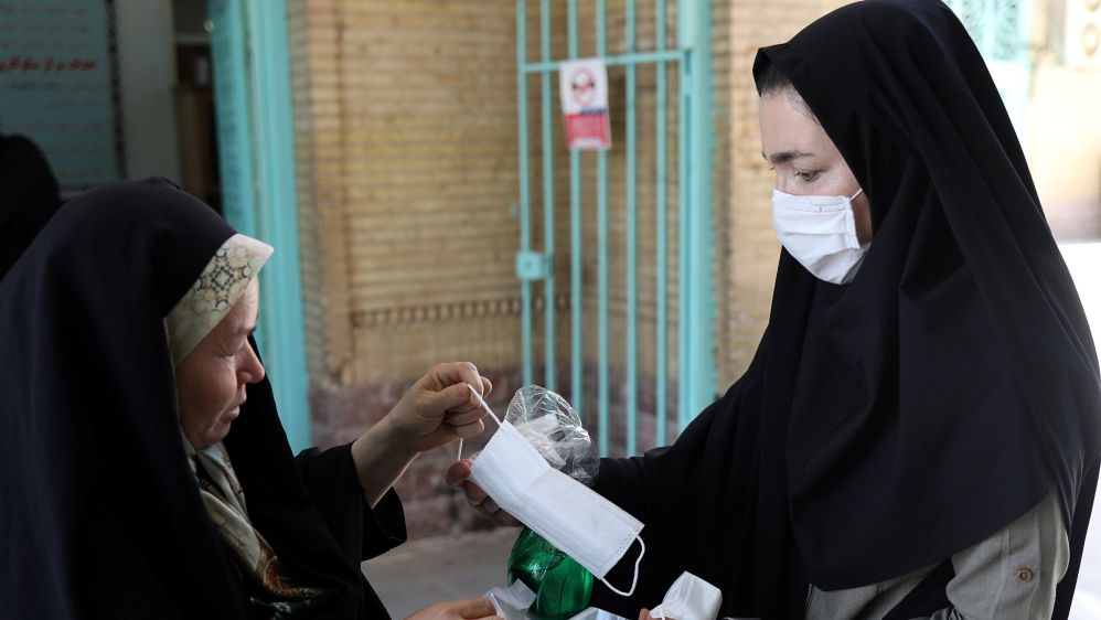 An Iranian woman gives a protective face mask to a worshipper to attend the Friday prayers in Qarchak Jamee Mosque, following the outbreak of the coronavirus disease (COVID-19)