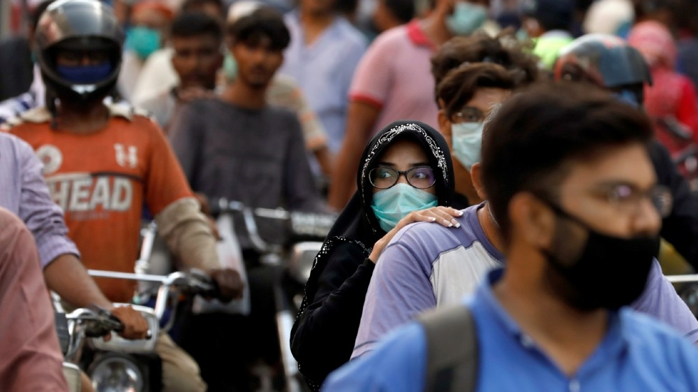 A woman rides on a motor bike as she wears a protective face mask amid the rush of people outside a market as the outbreak of the coronavirus disease (COVID-19) continues,