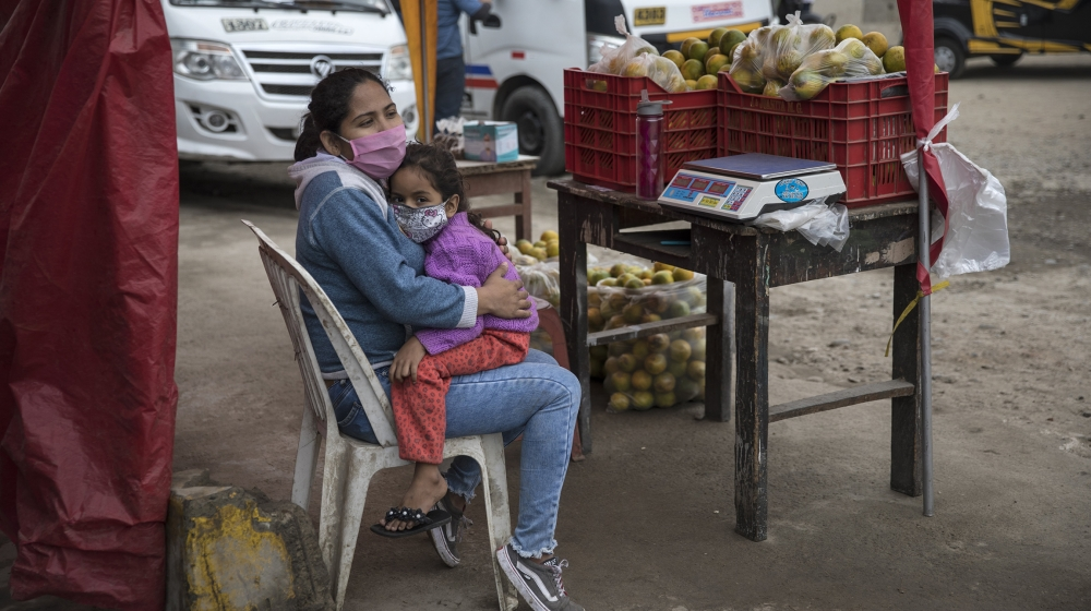 Wearing a mask to prevent the spread of the new coronavirus, Maria Garcia embraces her daughter Sofia, while selling oranges on a street in Lima, Peru, Thursday, June 4, 2020. (AP Photo/Rodrigo Abd)