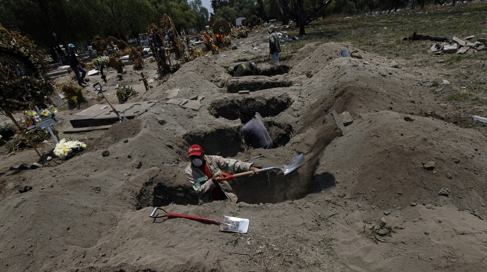 Melvin Sanaurio, front, digs a grave at the San Lorenzo Tezonco Iztapalapa cemetery in Mexico City, Tuesday, June 2, 2020, amid the new coronavirus pandemic.