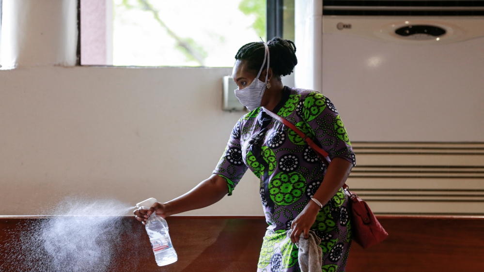 A worker sprays disinfectant on the chairs, after a church service as worship centers were reopened following the ease of restrictions imposed to curb the spread of the coronavirus disease in Abuja