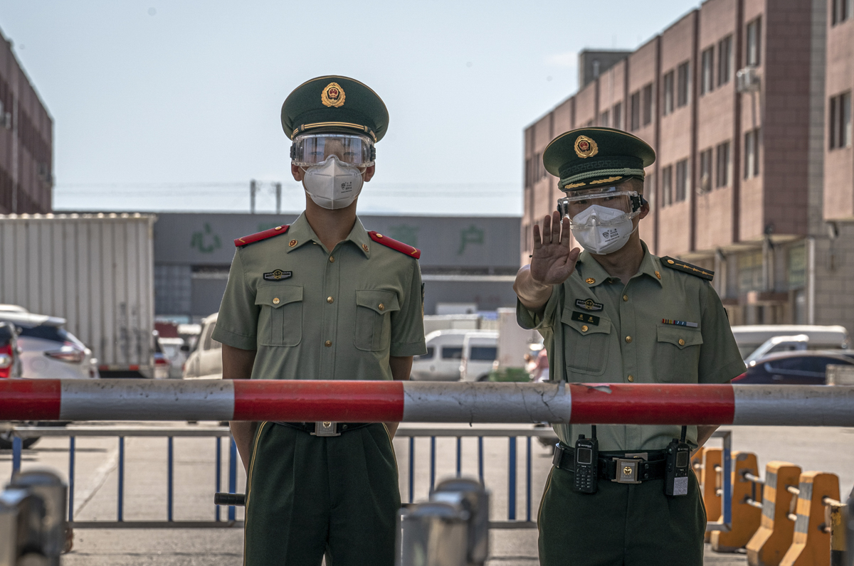 Police officers stand guard next to the closed Xinfadi market in Fengtai district, Beijing. [Roman Pilipey/EPA]
