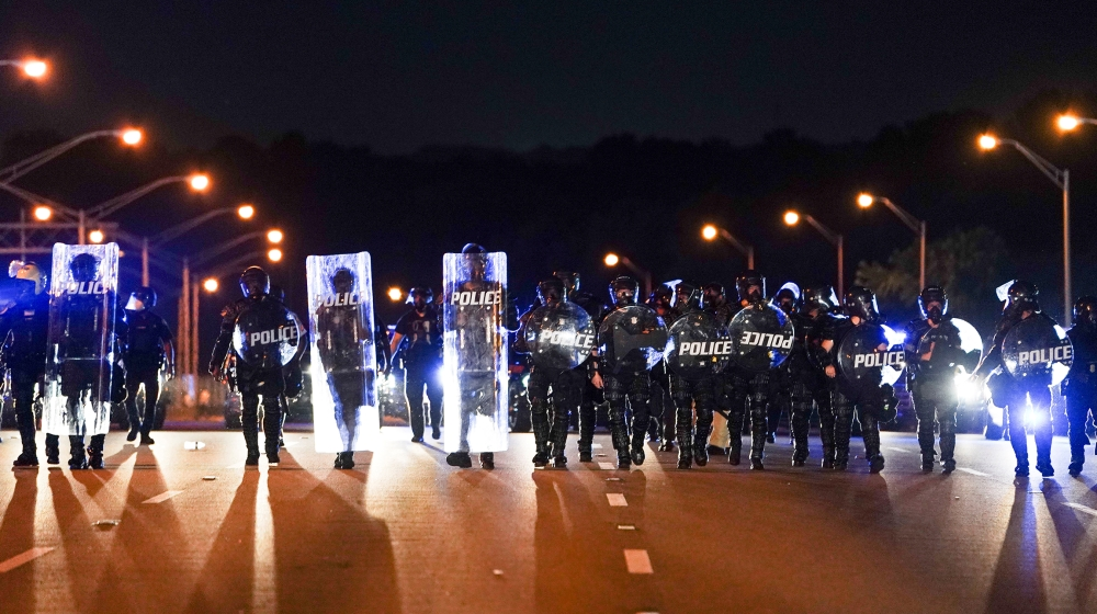Police with riot shields advance to detain protesters for blocking traffic on a freeway during a rally against racial inequality and the police shooting death of Rayshard Brooks, in Atlanta, Georgia,