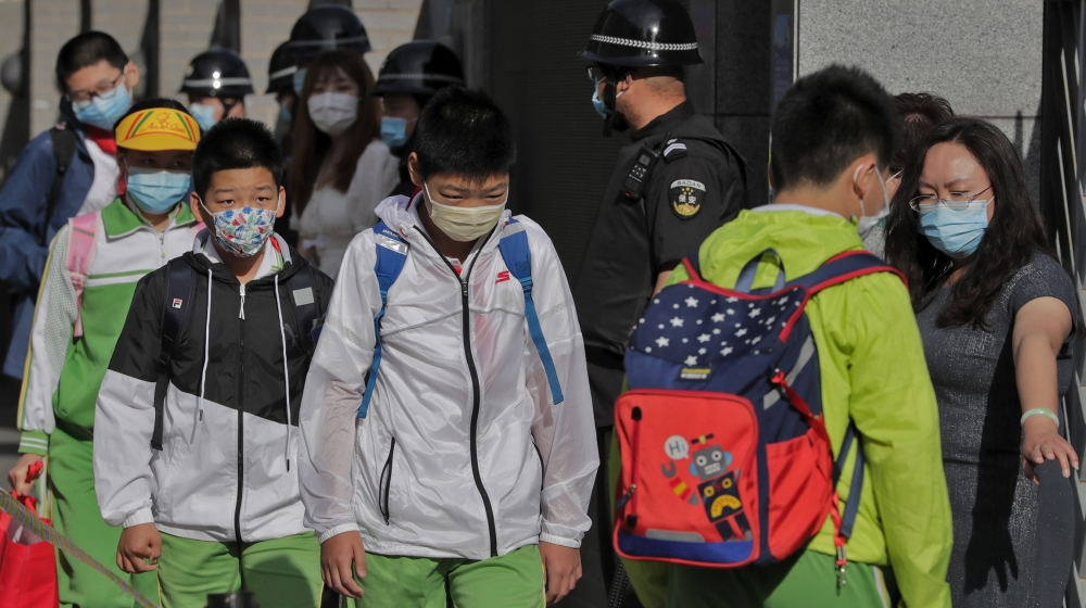 Students wearing protective face masks to help curb the spread of the new coronavirus are directed by a teacher to keep their social distancing as they arrive for the reopening of a primary school in