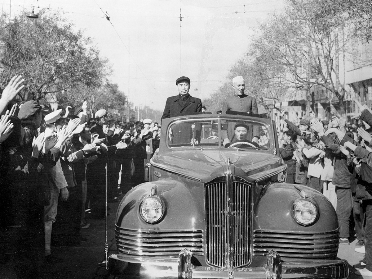 (Original Caption) Prime Minister Jawaharlal Nehru of India is shown, (R), being cheered by crowds that lined the route from the airfield where he landed to the city of Peiping, the capitol of Red Chi