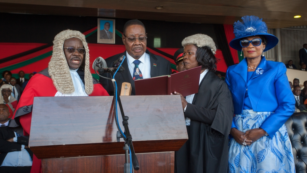 Malawi's President elect Arthur Peter Mutharika is sworn in for his second term by Chief Justice Andrew Nyirenda (L) and Registrar of the high Court and Supreme court of appeal Agnes Patemba (R) at K
