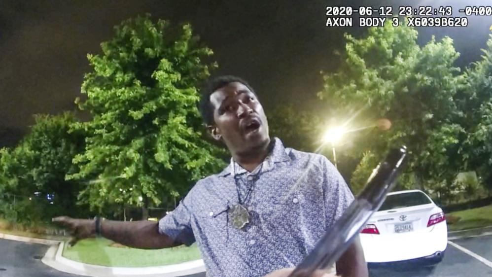 This screen grab taken from body camera video provided by the Atlanta Police Department shows Rayshard Brooks speaking with Officer Garrett Rolfe as Rolfe writes notes during a field sobriety test in