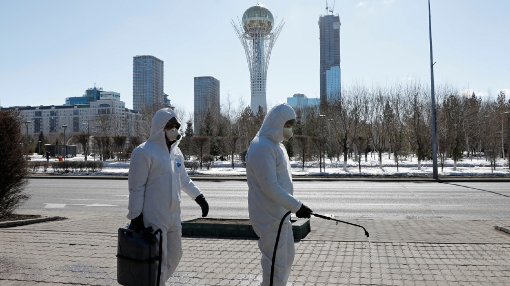 Workers wearing protective suits spray disinfectant on the street to prevent the spread of coronavirus disease (COVID-19), in central Nur-Sultan, Kazakhstan March 24, 2020.