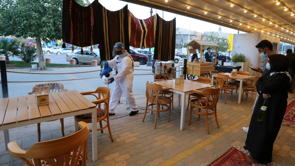 A worker wears a protective suit, following the outbreak of the coronavirus disease (COVID-19), sterilizes the tables before the customers sit down at a restaurant, in Riyadh