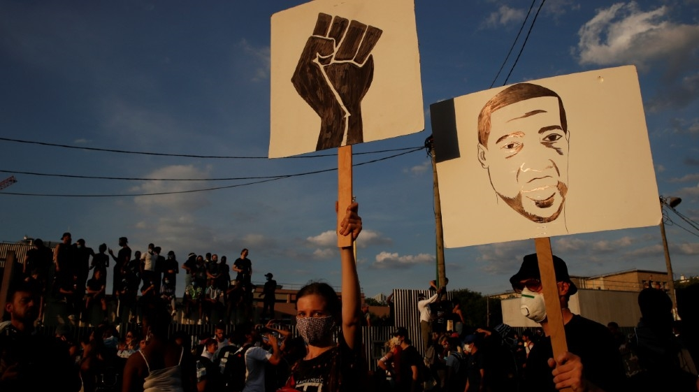 Protesters holding placards attend a banned demonstration planned in memory of Adama Traore, a 24-year old black Frenchman who died in a 2016 police operation which some have likened