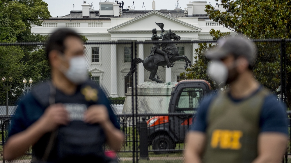 The White House is visible behind a large security fence as uniformed Secret Service and FBI agents stand on the street in front of Lafayette Park in the morning hours in Washington, Tuesday, June 2,