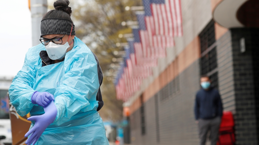 An Emergency Medical Technician (EMT) dons personal protective equipment before going into Elmhurst Hospital during the ongoing outbreak of the coronavirus disease (COVID-19) in the Queens borough of