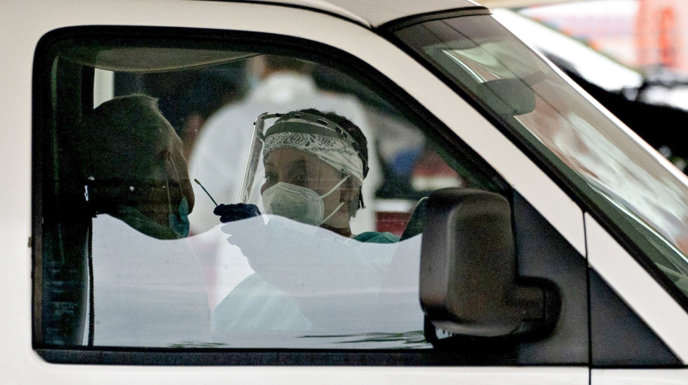 A coronavirus test is administered by a healthcare worker at a drive-thru coronavirus testing site hosted by Arlington County and the Commonwealth of Virginia in Arlington, Virginia, U.S., on Friday,