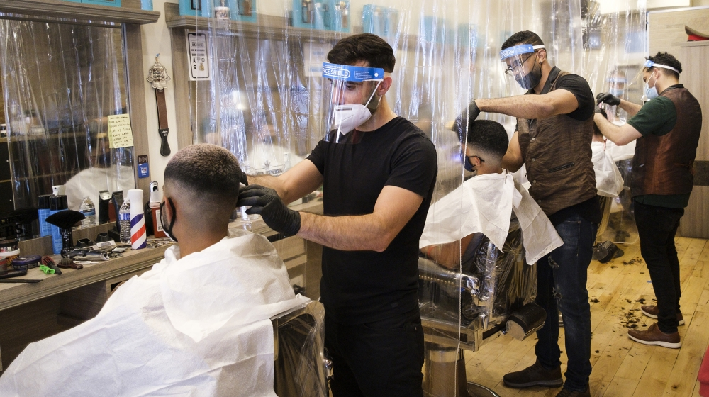 Barbers wear protective equipment and clients sit in chairs separated by plastic dividers at Hell's Kitchen Barbers on the first day that hair salons could reopen as part of Phase 2 in New York, New Y