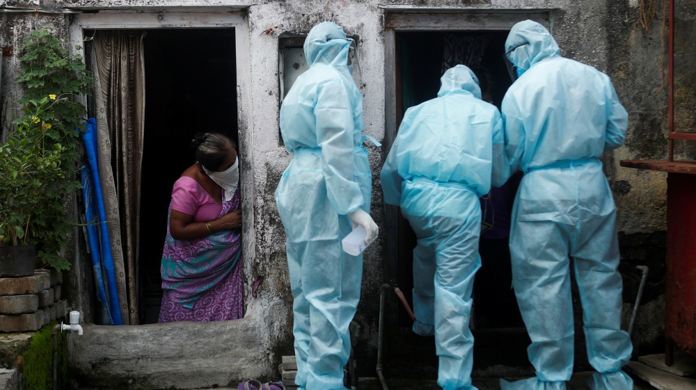A woman watches as healthcare workers check the temperature of residents of a slum, in Mumbai