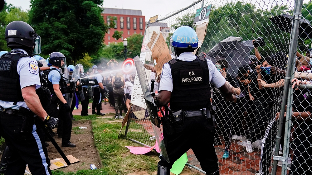 U.S. Park Police officers deploy pepper spray as they clash with protestors during an attempt to pull down the statue of U.S. President Andrew Jackson in the middle of Lafayette Park in front of the W
