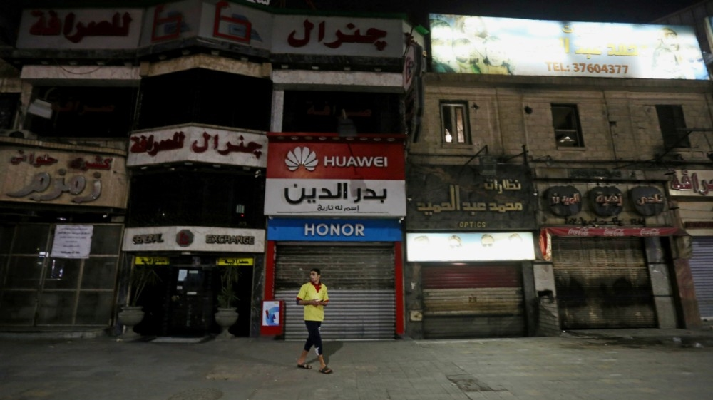 A man walks in front of closed shops, after Egyptian Prime Minister Mostafa Madbouly ordered all restaurants, cafes, cafeterias, night clubs, shopping malls and shops