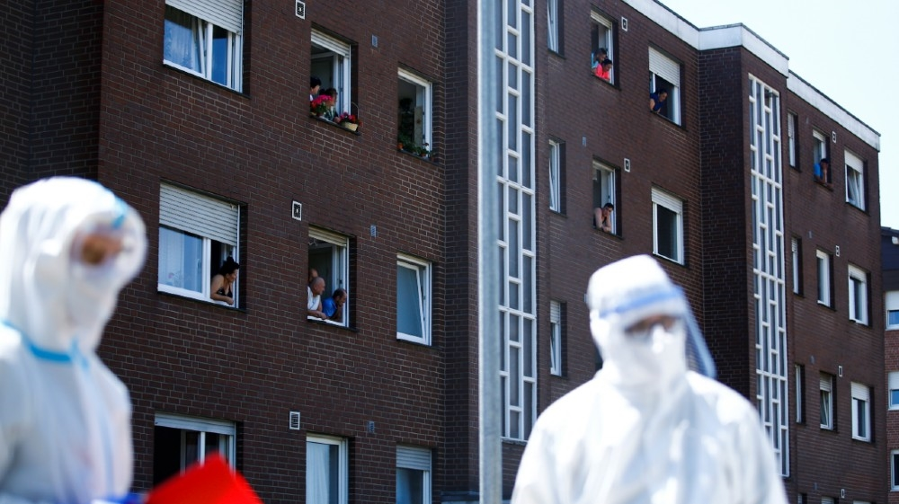Employees of the Toennies factory, who are under lockdown after a coronavirus disease (COVID-19) outbreak in the meatpacking plant, lean out the windows of their houses in Verl,