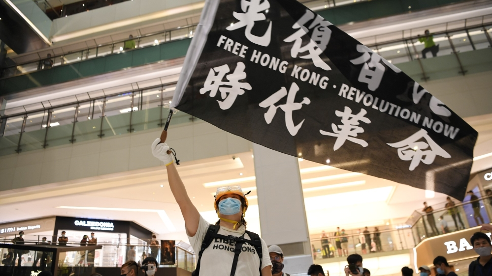 Pro-democracy protesters waves a banner during a protest at the New Town Plaza mall in Sha Tin in Hong Kong