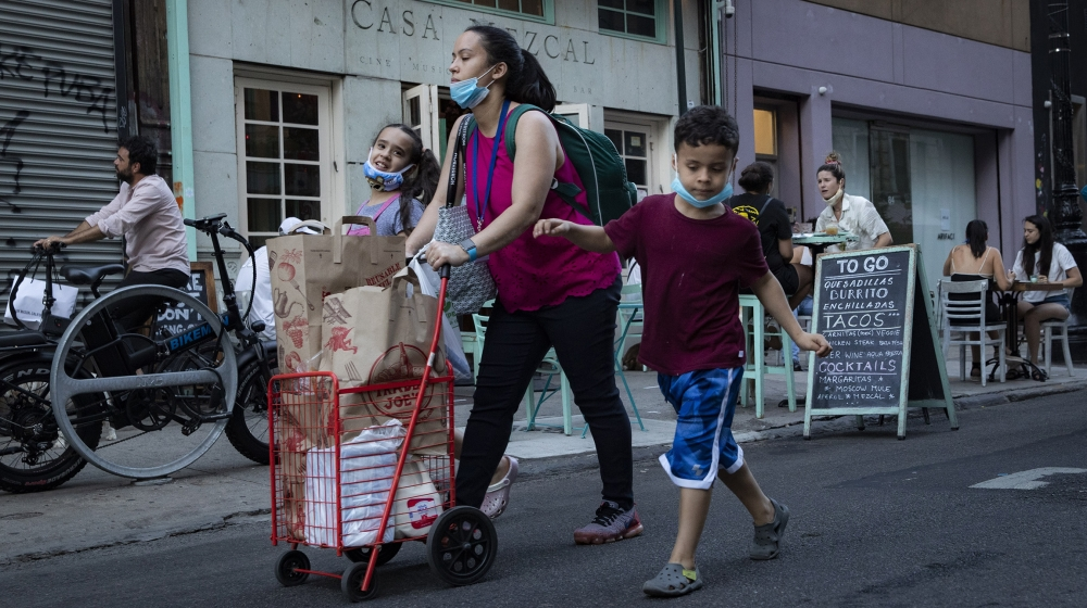 Pedestrians pass customers dining outside Casa Mezcal, Monday, June 22, 2020, in New York. New York City ventured into a crucial stage of reopening as stores let people in Monday, offices brought work