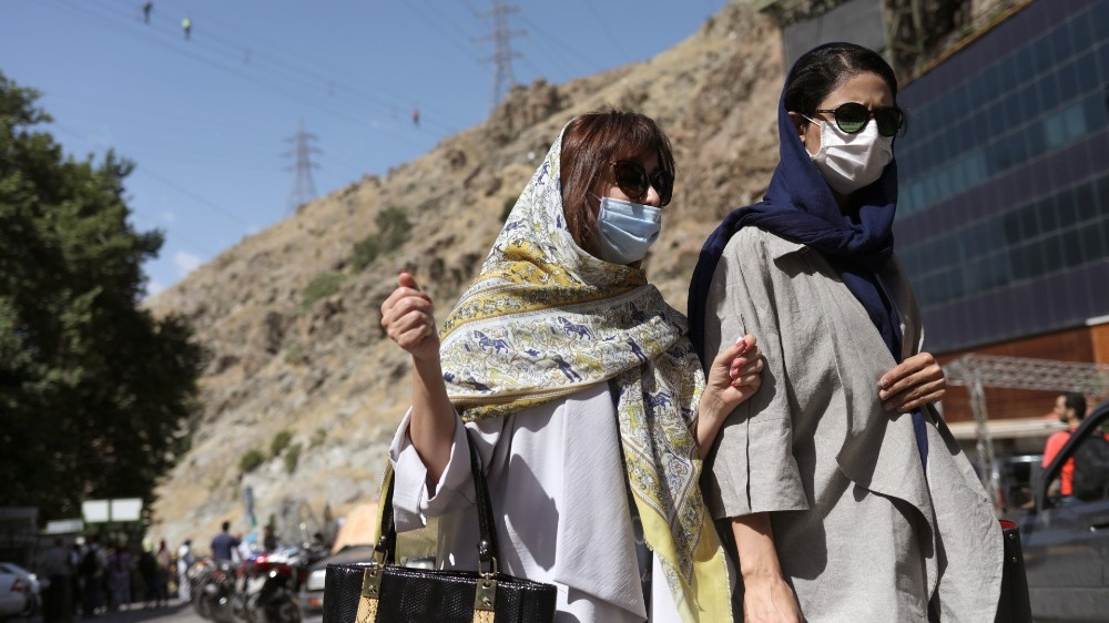 Iranian women wearing protective face masks walk in Darband street