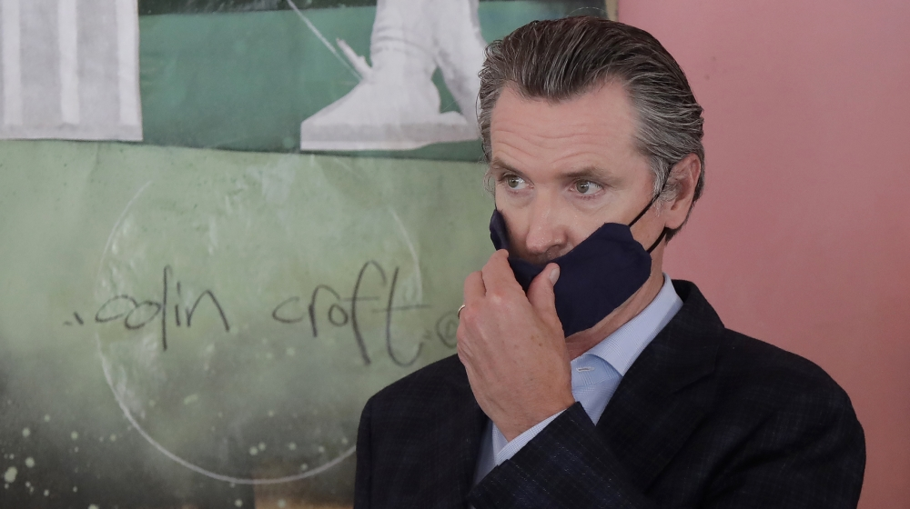 California Governorn Gavin Newsom adjusts his mask while speaking to reporters at Miss Ollie's restaurant amid the coronavirus pandemic in Oakland, California, USA, 09 June 2020. EPA-EFE/JEFF CHIU / A