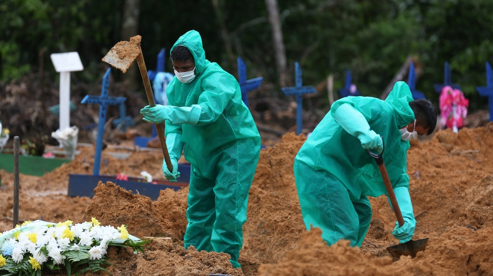 Cemetary workers dig graves for victims and suspected victims of the COVID-19 coronavirus pandemic at the Nossa Senhora cemetary in Manaus, Amazon state, Brazil on May 6, 2020. MICHAEL DANTAS / AFP