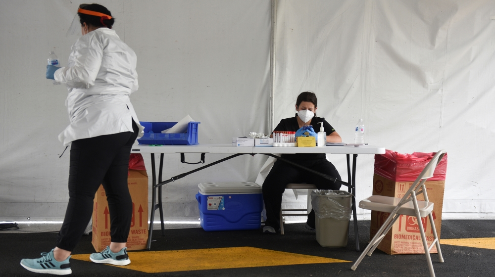 Medical workers coordinate testing as dozens of people wait in their cars at United Memorial Medical Center amid the global outbreak of the coronavirus disease (COVID-19), in Houston, Texas, U.S., Jun