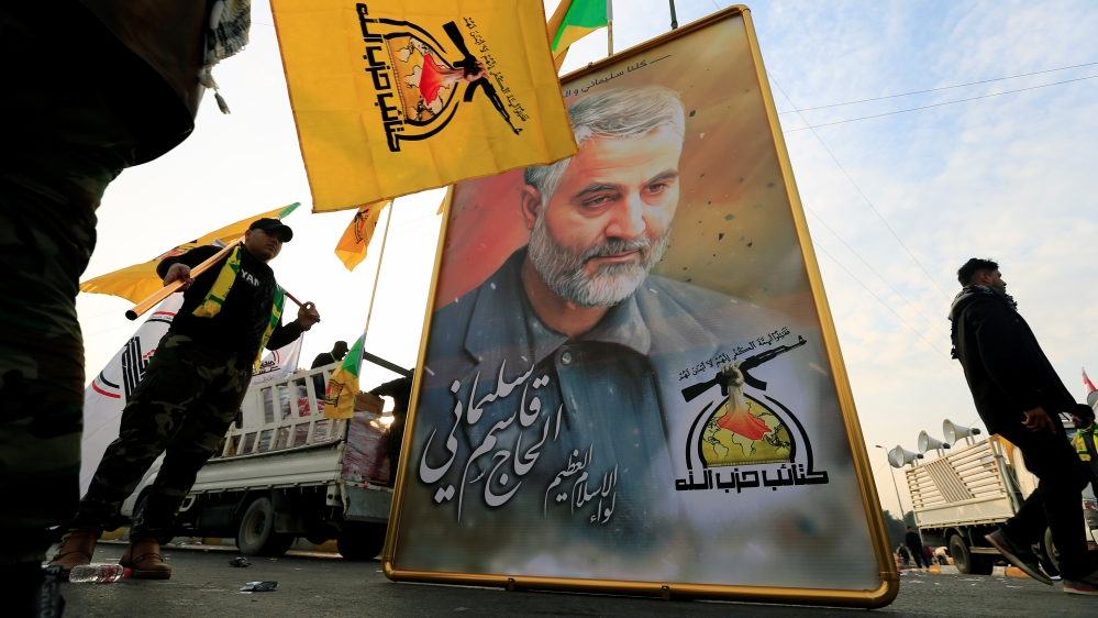 Kataib Hezbollah Iraqi militia hold the picture of the Iranian Major-General Qassem Soleimani, as they gather ahead of the funeral of the Iraqi militia commander Abu Mahdi al-Muhandis, in Baghdad