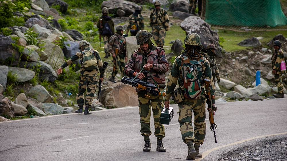 Indian Border Security Force (BSF) soldiers patrol a highway as Indian army convoy passes through on a  highway leading towards Leh, bordering China, on June 19, 20