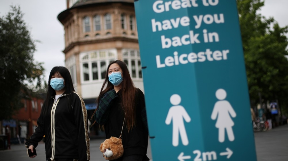 People wearing protective masks walk past a sign, amid the coronavirus disease (COVID-19) outbreak, in Leicester, Britain, June 29, 2020. REUTERS/Carl Recine