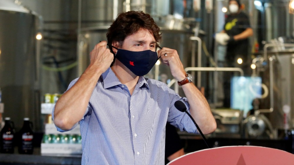 FILE PHOTO: Canada's Prime Minister Justin Trudeau removes his face mask as he visits the Big Rig Brewery, which utilizes the Canada Emergency Wage Subsidy given to businesses affected