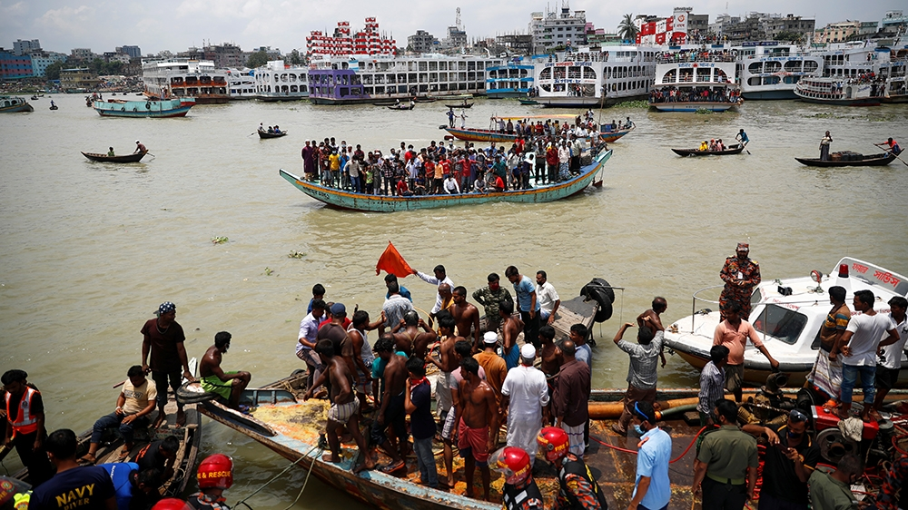 People on a boat watch the spot where a passenger ferry capsized in the river Buriganga in Dhaka, Bangladesh, June 29, 2020. REUTERS/Mohammad Ponir Hossain