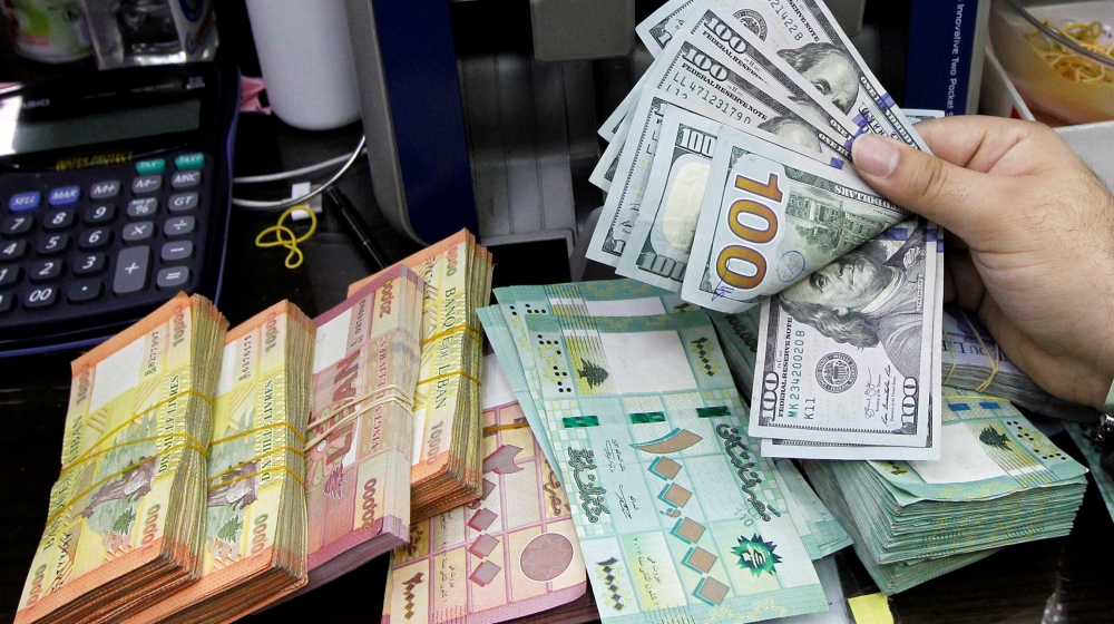 A man counts U.S. dollar banknotes next to Lebanese pounds at a currency exchange shop in Beirut, Lebanon April 24, 2020. REUTERS/Mohamed Azakir//File Photo