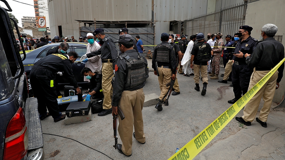 Members of the Crime Scene Unit of Karachi Police prepare to survey the site of an attack at the Pakistan Stock Exchange entrance in Karachi June 29, 2020. REUTERS/Akhtar Soomro