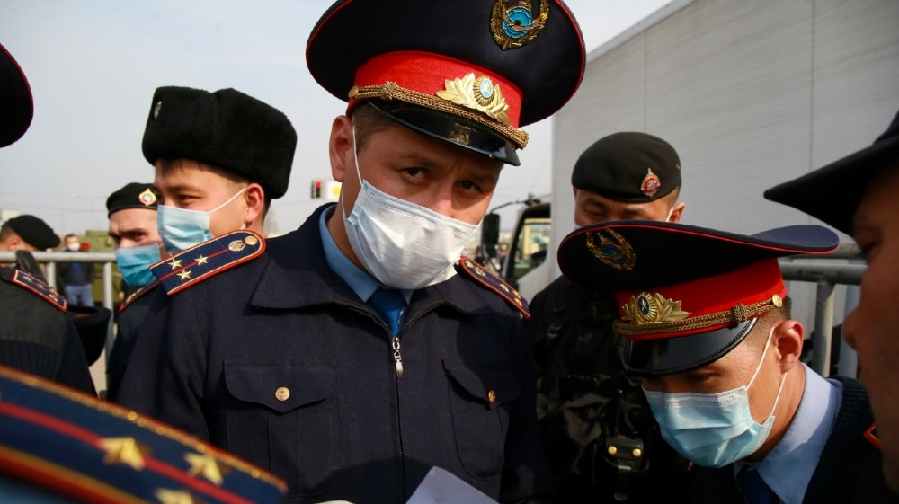 Law enforcement officers wearing face masks are seen on duty at a checkpoint on the outskirts of Almaty on March 19, 2020, after authorities locked down the city to contain the spread