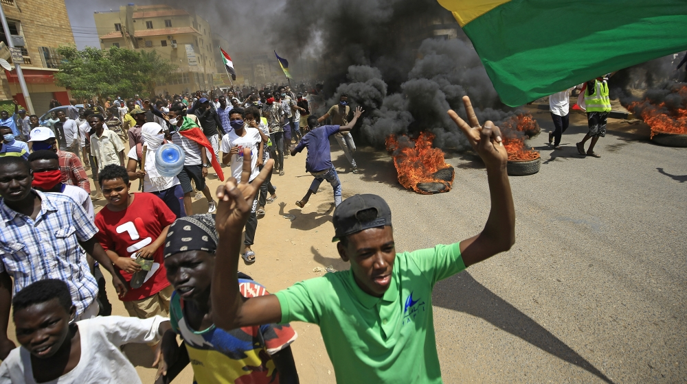 Sudanese demonstrators march while smoke billows from burning tyres during a protest on Sixty street in the east of the capital Khartoum, on June 30, 2020. Tens of thousands of Sudanese took to the st