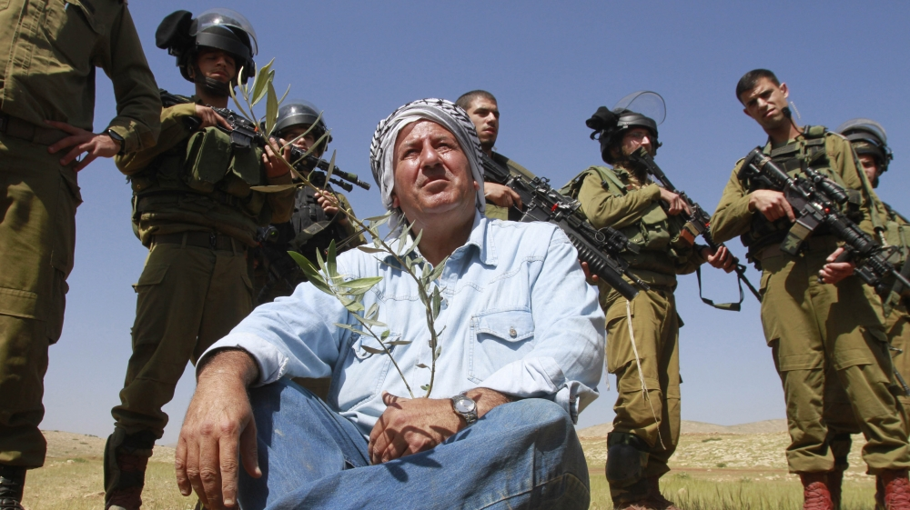 Israeli soldiers stand guard as a Palestinian farmer sits on the ground after planting olive trees during a protest in the Jordan Valley