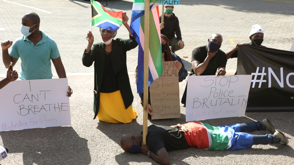 Protesters hold placards as they demonstrate against the death in Minneapolis police custody of George Floyd and Collins Khoza, in Pretoria