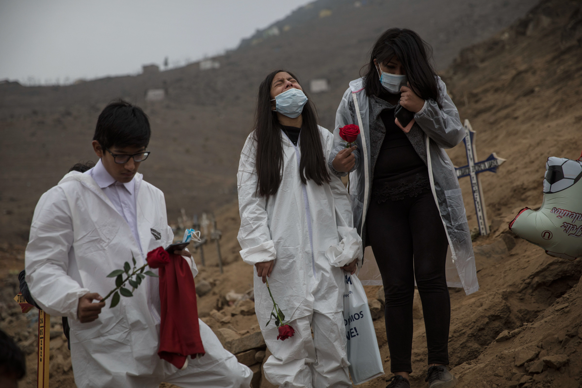 Dayra Montalbo, centre, 12, cries next to her sister Valeria, 18, and brother Carlos, 16, during the burial of their father Carlos Montalbo, 45, who died from COVID-19 complications. Carlos Montalbo Sr died at his home after several calls from his relatives to the telephone number of the Ministry of Health, which they say never answered. [Rodrigo Abd/AP Photo]
