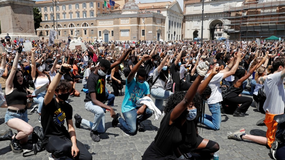 Demonstrators raise their fists as they attend a protest against racial inequality in the aftermath of the death in Minneapolis police custody of George Floyd, at Piazza del Popolo