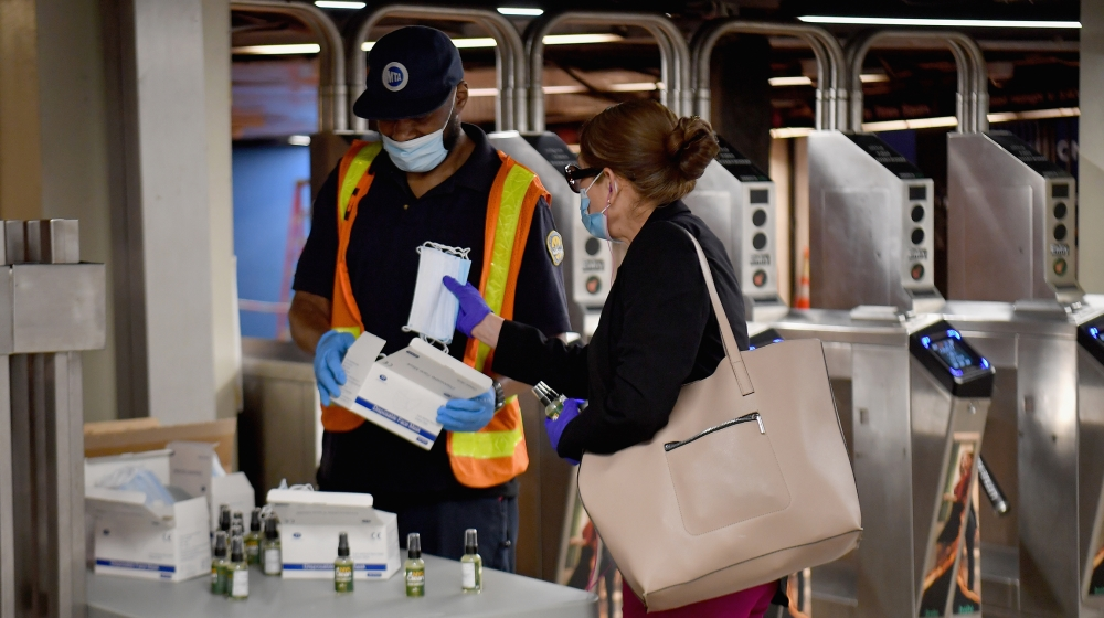 An MTA worker hands out free hand sanitizer and face masks at the Grand Central Station subway during morning rush hour
