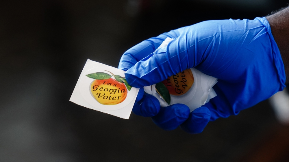 A polling place worker holds an