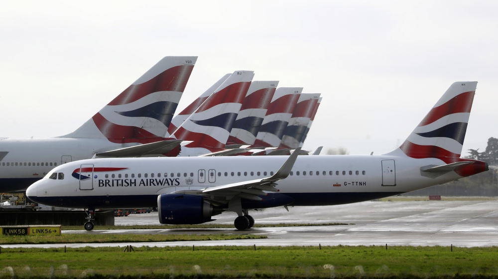 A British Airways plane taxis past tail fins of parked aircraft to the runway near Terminal 5 at Heathrow Airport in London, Britain March 14, 2020. REUTERS/Simon Dawso