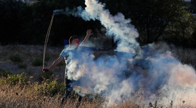 A Palestinian demonstrator returns a tear gas canister during a protest against Israel's plan to annex parts of the Israeli-occupied West Bank, near the Jewish settlement of Beit El near Ramallah July