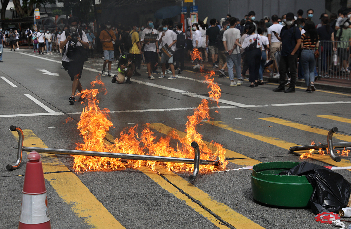 Protesters set fire to a barricade in an attempt to block a road during a rally against the new national security law in Causeway Bay. [Jerome Favre/EPA]
