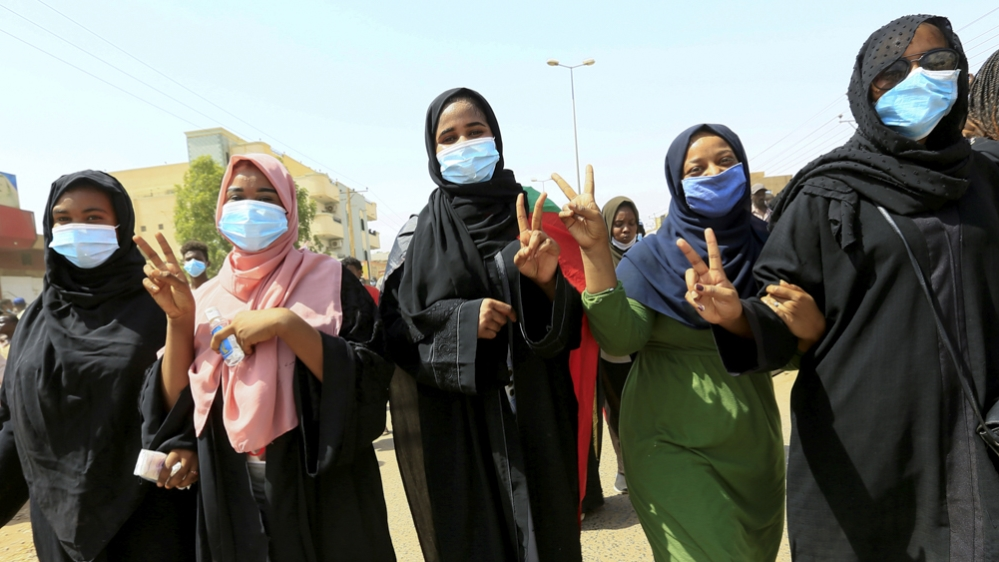 Civilians chant slogans as members of Sudanese pro-democracy protest on the anniversary of a major anti-military protest, as groups loyal to toppled leader Omar al-Bashir plan rival demonstrations in